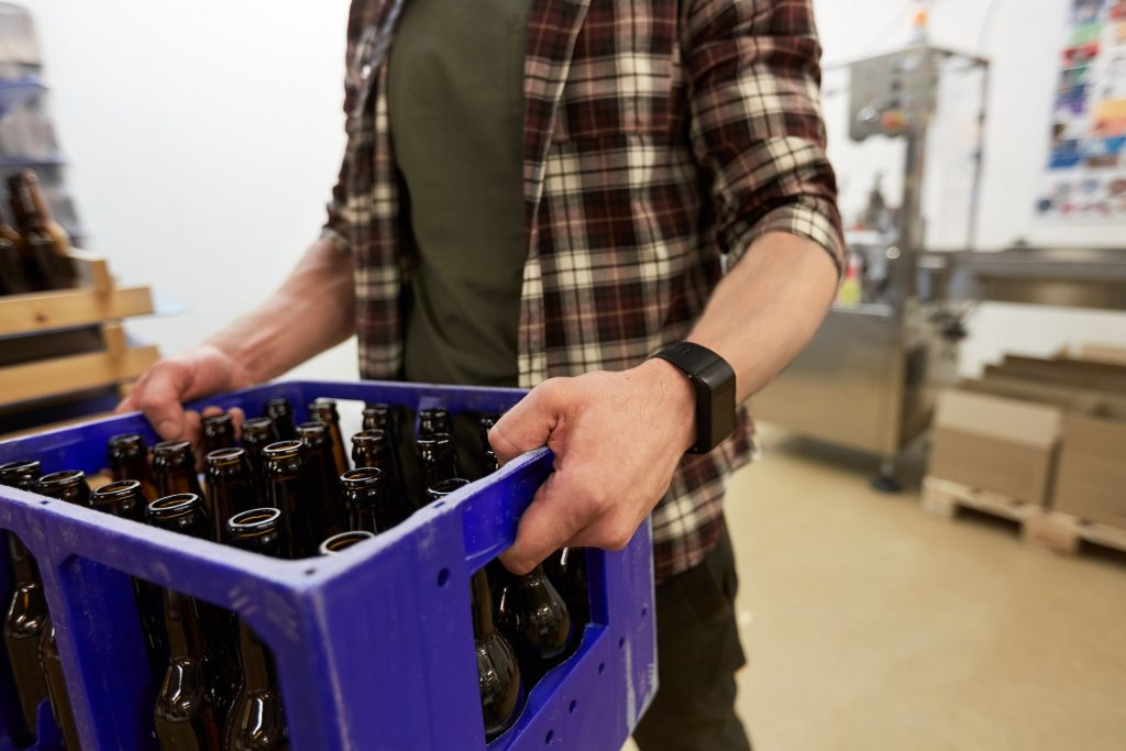 man with bottles in box at craft beer brewery